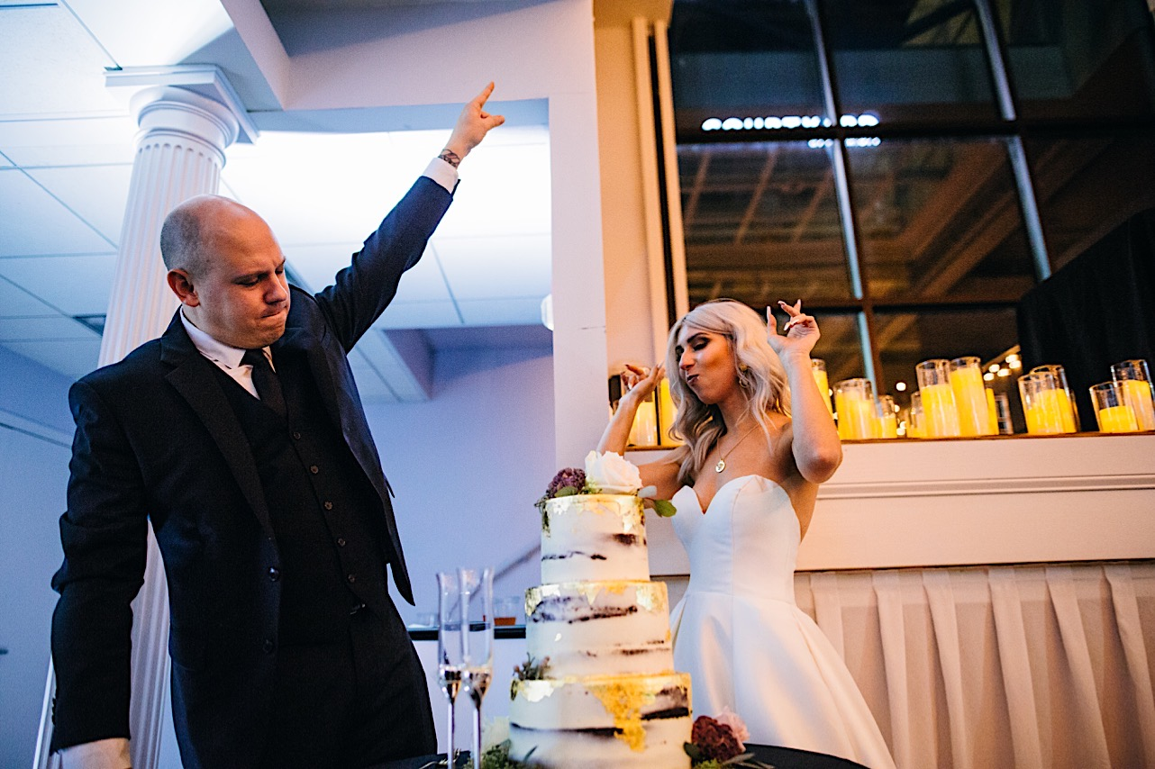 bride and groom dance around their cake at their halloween elopement