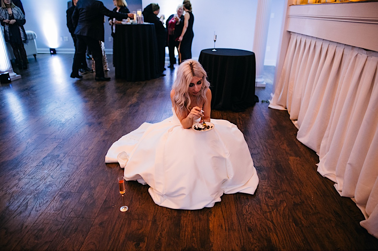 bride crouches down on the floor as she eats a slice of cake at her halloween elopement