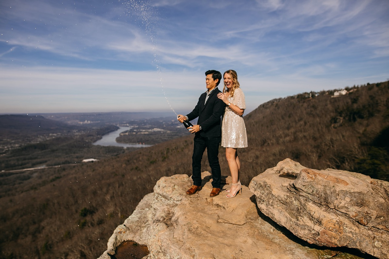 An engaged couple pops a bottle of champagne on Sunset Rock near Chattanooga, TN.
