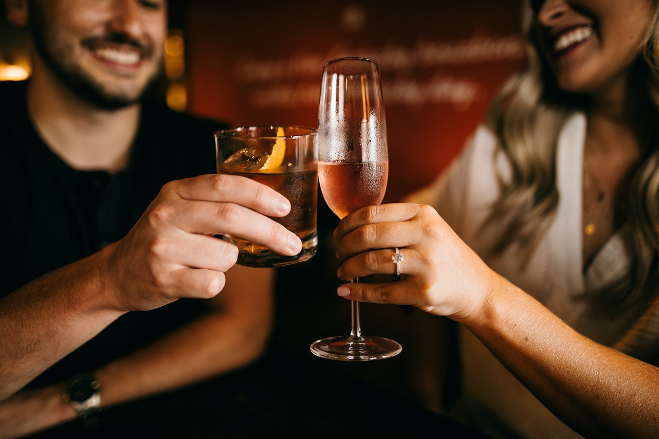A couple smile and cheers their drinks - an old fashioned and a glass of rosé - in their favorite bar.