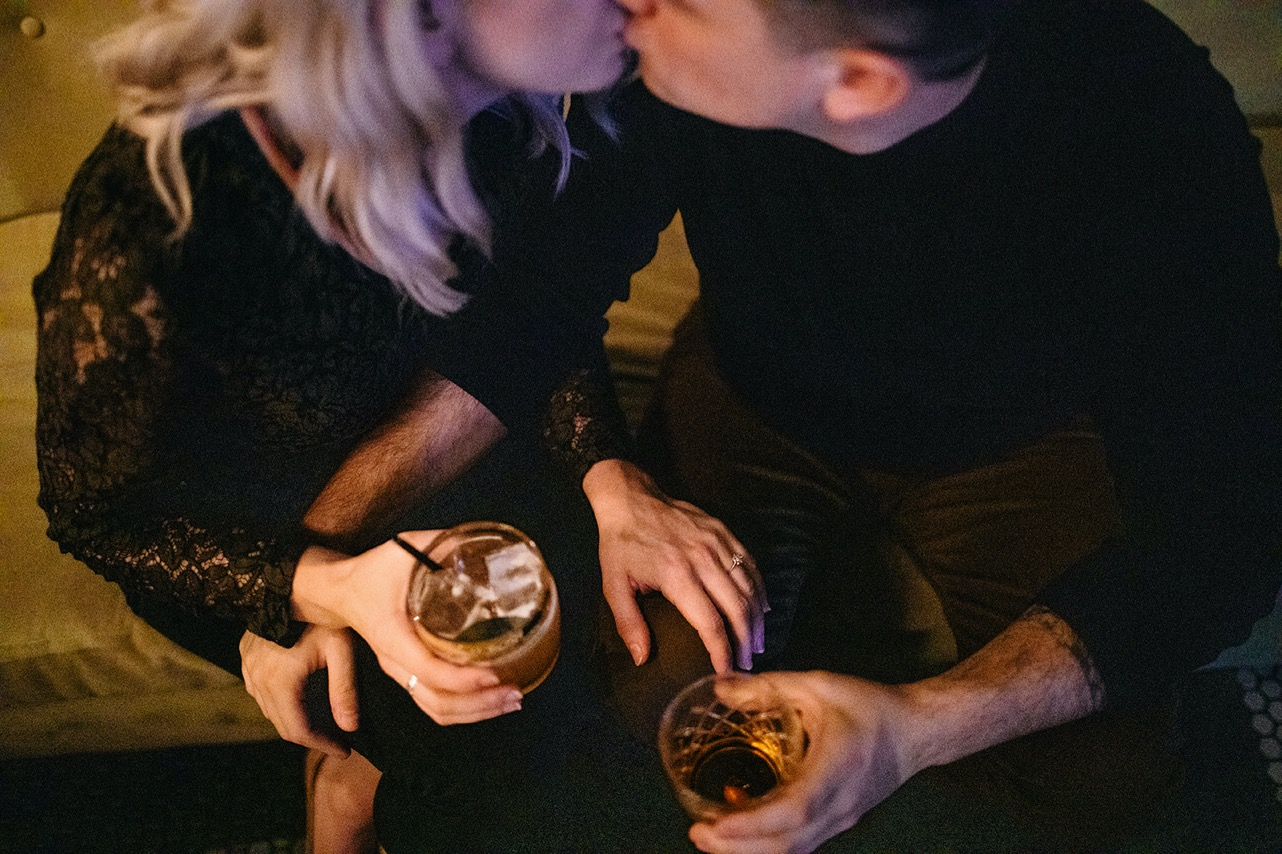 A couple sit together kissing and drinking whiskey on a mustard couch in a bar.