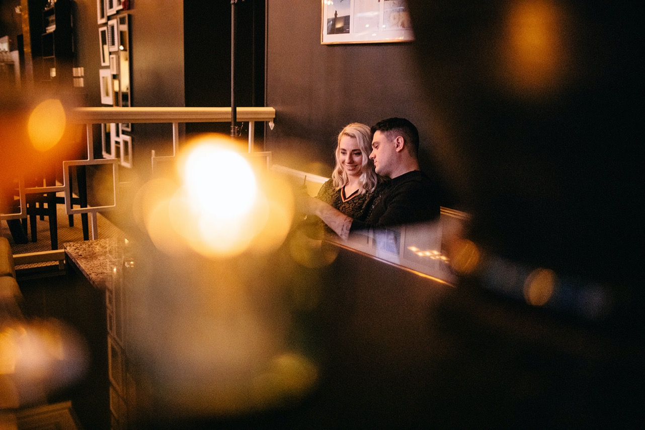 A couple sit together cuddling and drinking whiskey on a mustard couch in a bar.