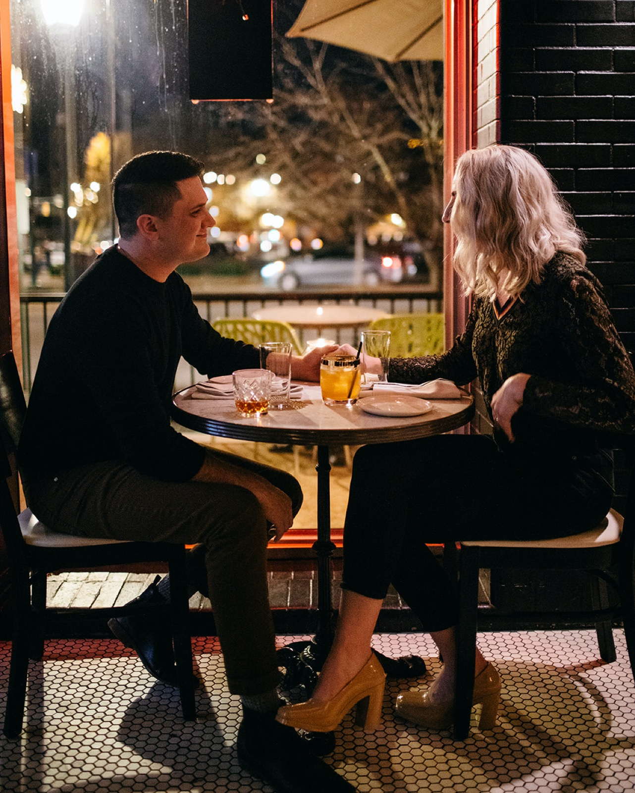 A couple hold hands across a small, round table in their favorite bar.