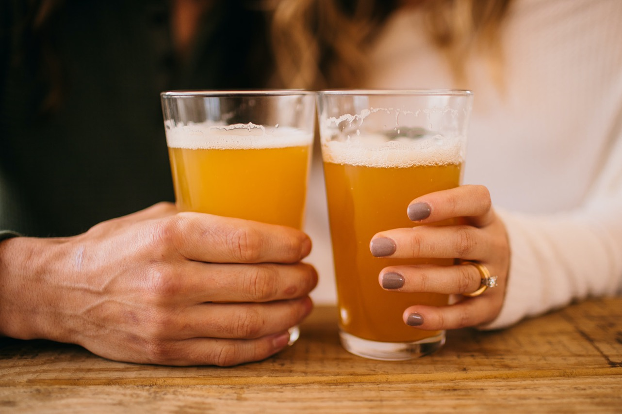 A close up of an engaged couple's hands holding pint glasses of beer.