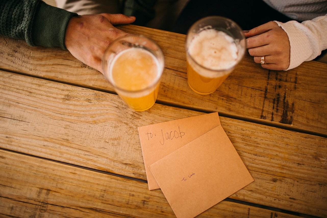 An engaged couple's hands on a picnic table with glasses of beer and love letters to each other.