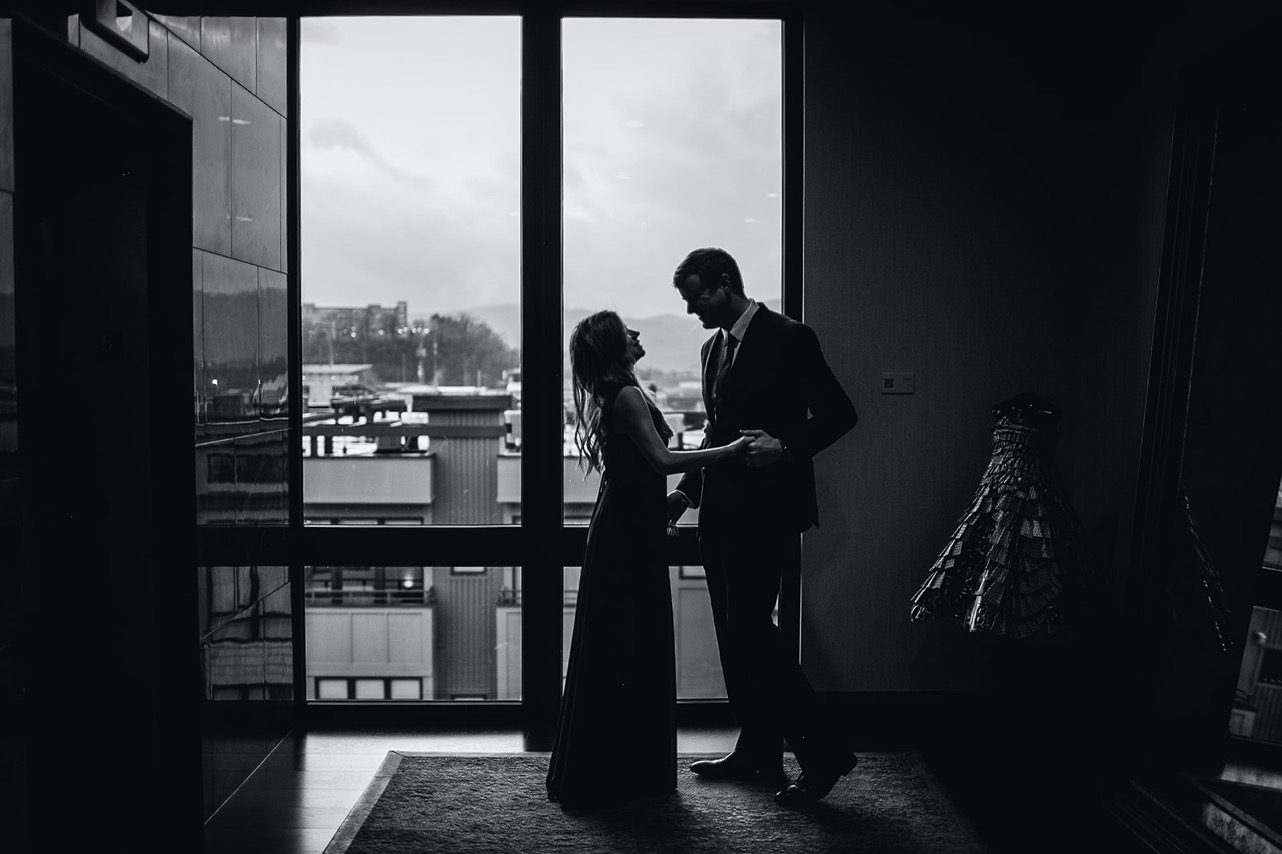 A couple dance together and smile at one another in front of a large window in their favorite bar.