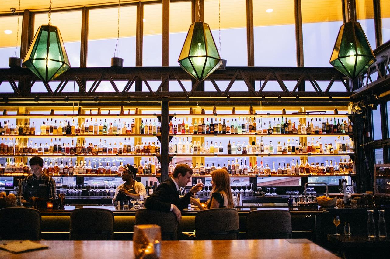 A couple drink together at a large, bottle-filled bar.