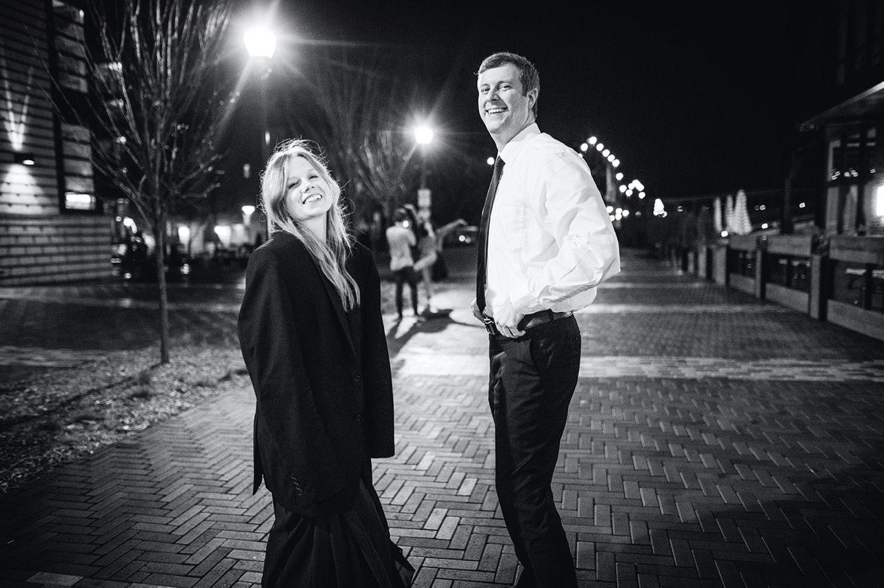 A man gives his fiancé his coat to wear on the streets of downtown Chattanooga at night.