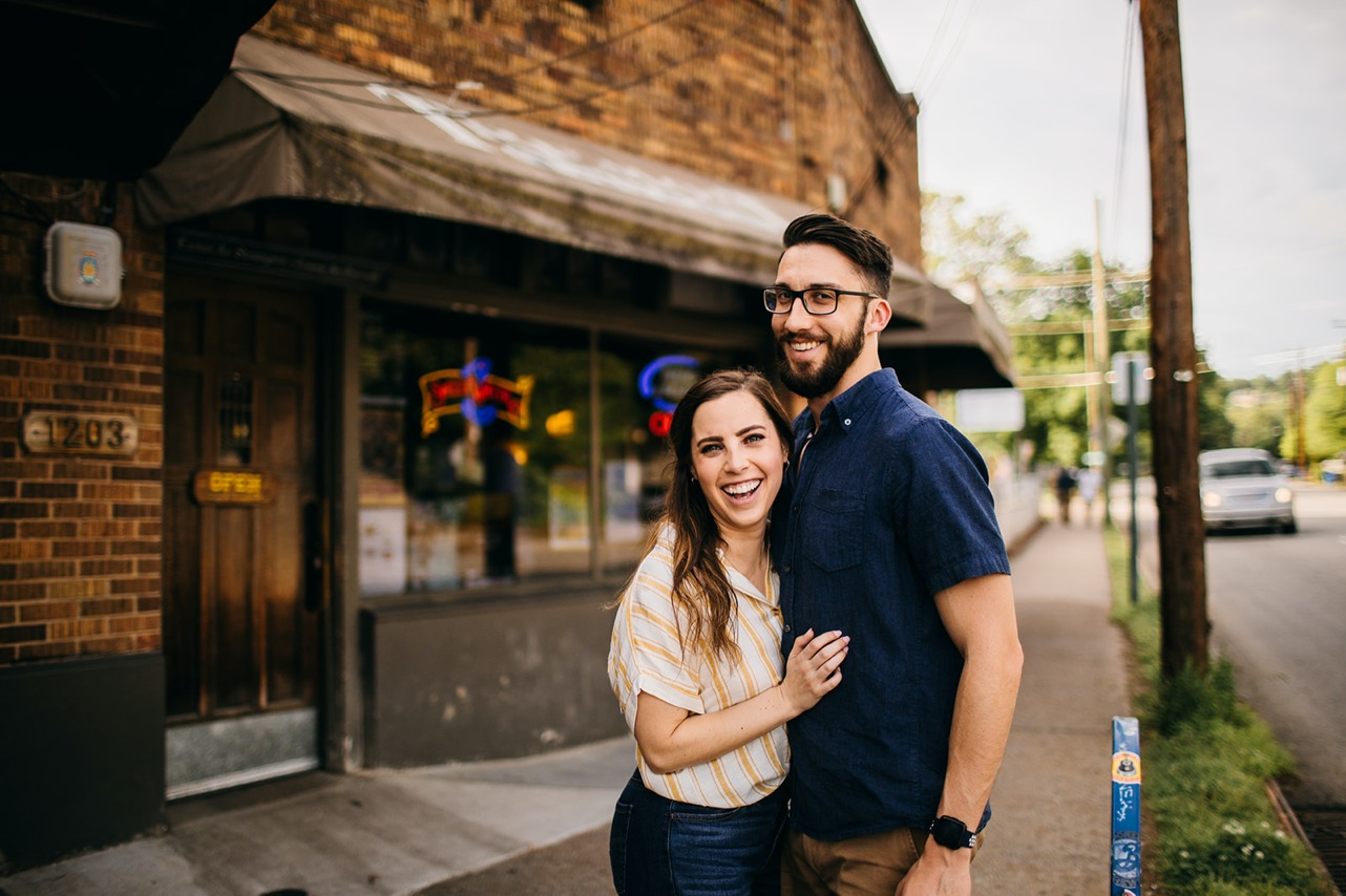 An engaged couple embrace and laugh outside their favorite bar.