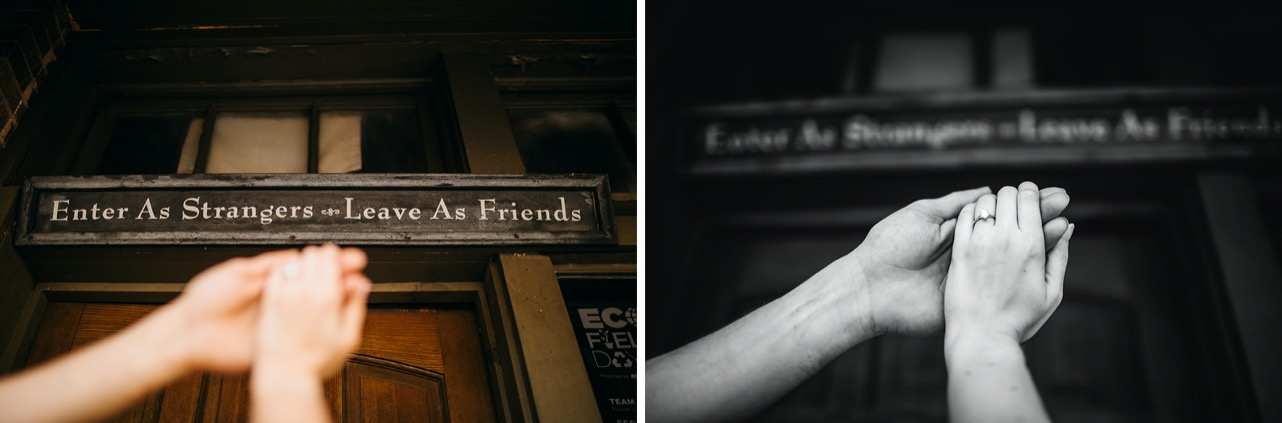 """A close-up of a man and woman holding hands in front of a sign that reads, """"Enter as strangers, leave as friends."""""""