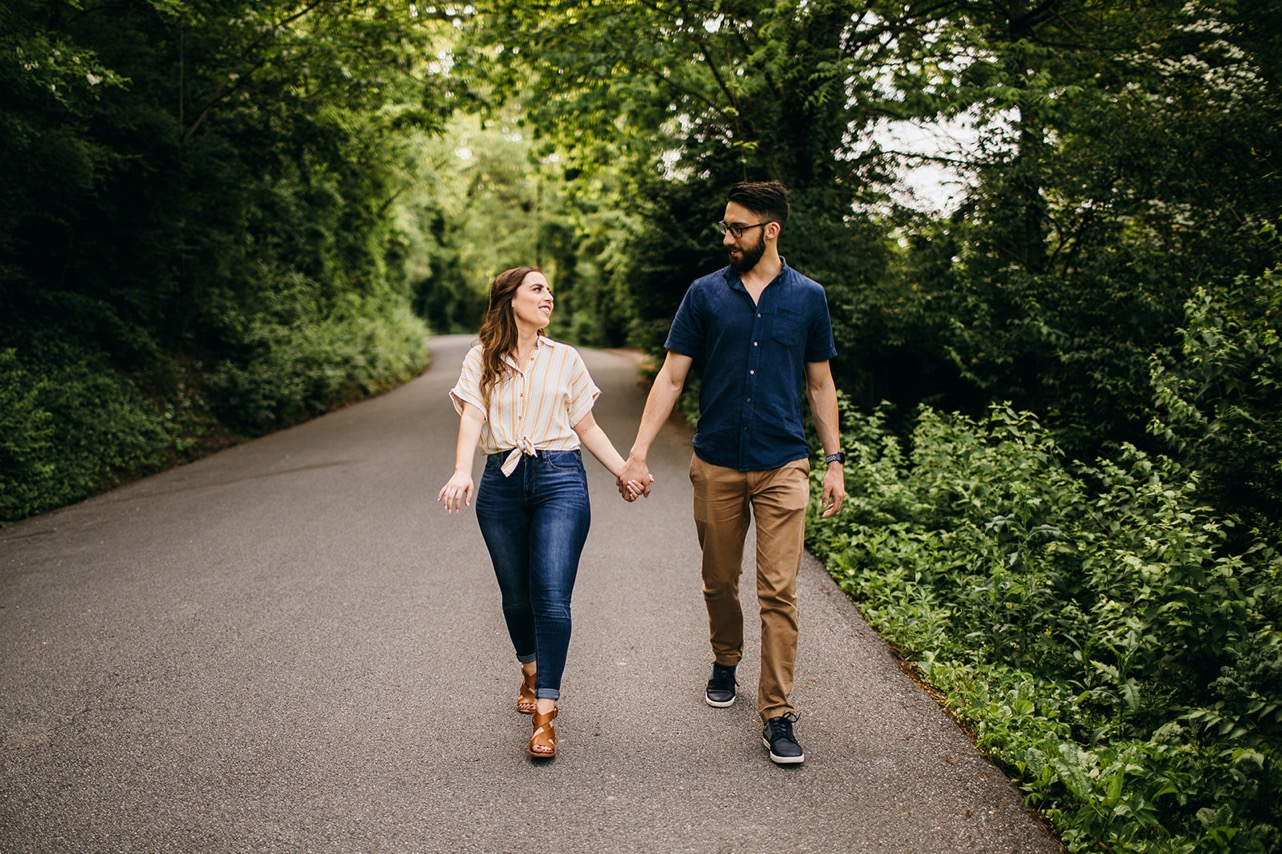 A couple walk hand-in-hand on a forested, paved path between engagement photo locations in Chattanooga.