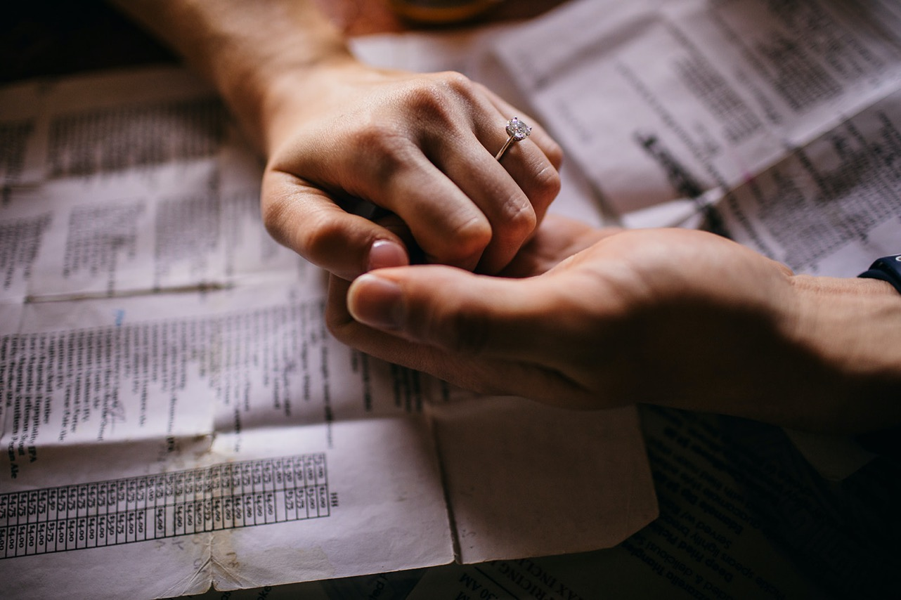 A close-up of an engaged couple holding hands atop paper bar menus.