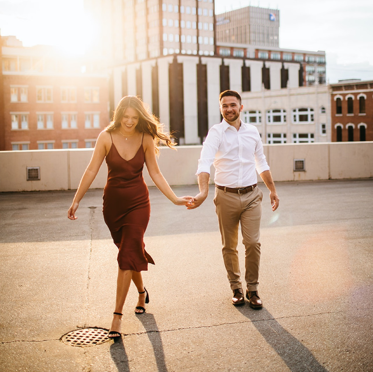 A couple walks hand-in-hand on a rooftop in downtown Chattanooga during their engagement photo session.