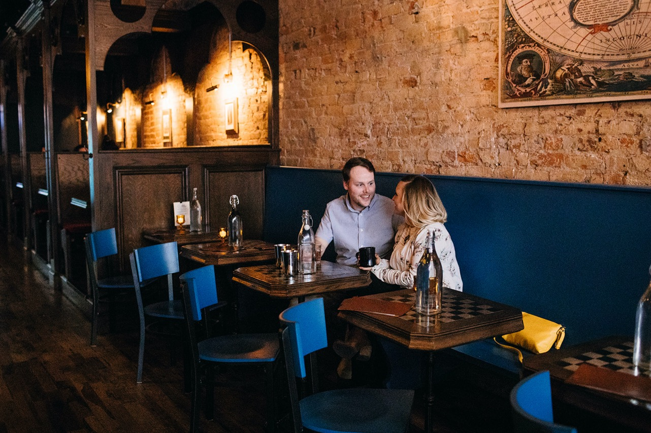 A couple sit together in a booth at a bar during their engagement photo session.