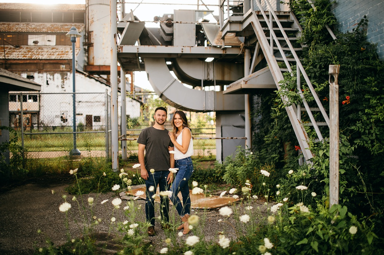 A couple pose and smile for the camera in an overgrown section of The Foundry in Chattanooga.