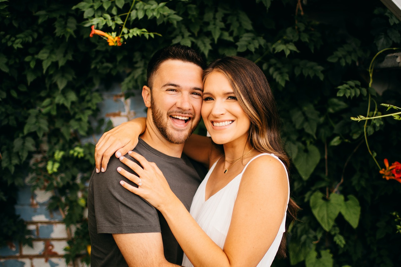 A couple embrace and smile for the camera in front of a vine-covered wall during their Chattanooga engagement photo session at The Foundry.