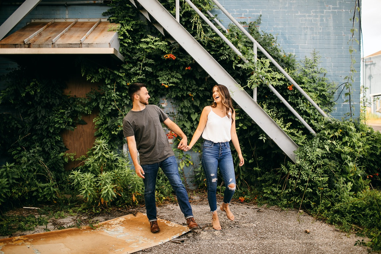 A man and woman laugh while standing hand-in-hand in front of a vine-covered wall.