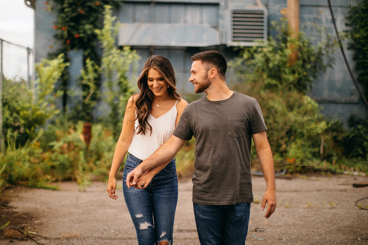 An engaged couple laugh and walk together at The Foundry in Chattanooga.