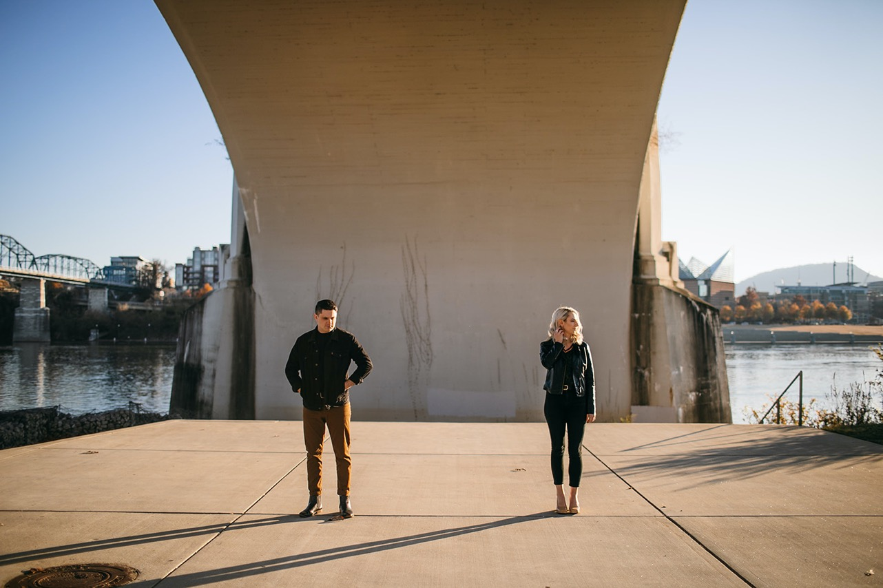 A couple stand apart from each other gazing in opposite directions under the Market Street Bridge in Chattanooga.