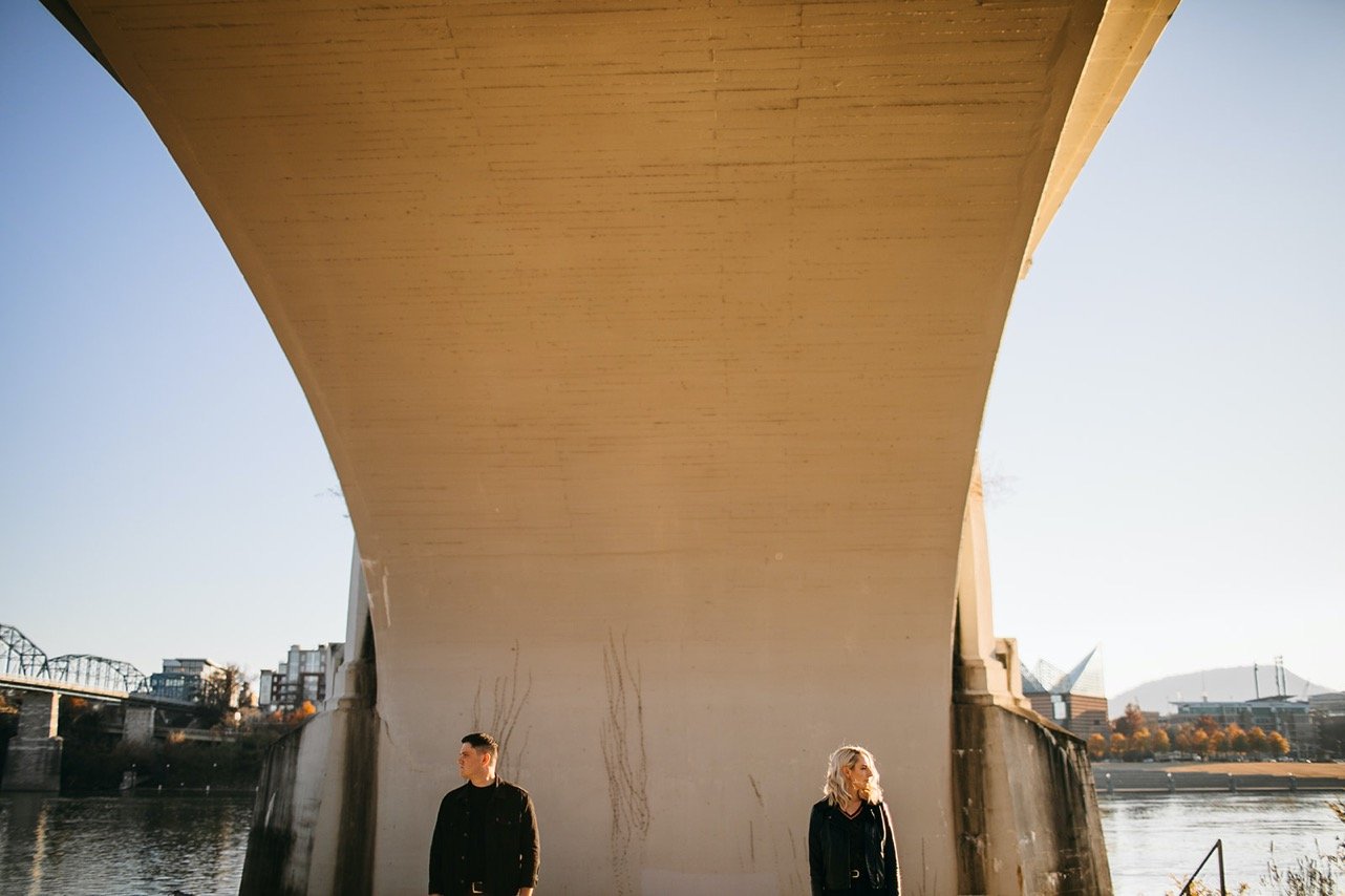 A couple stand far apart gazing in opposite directions under the Market Street Bridge.