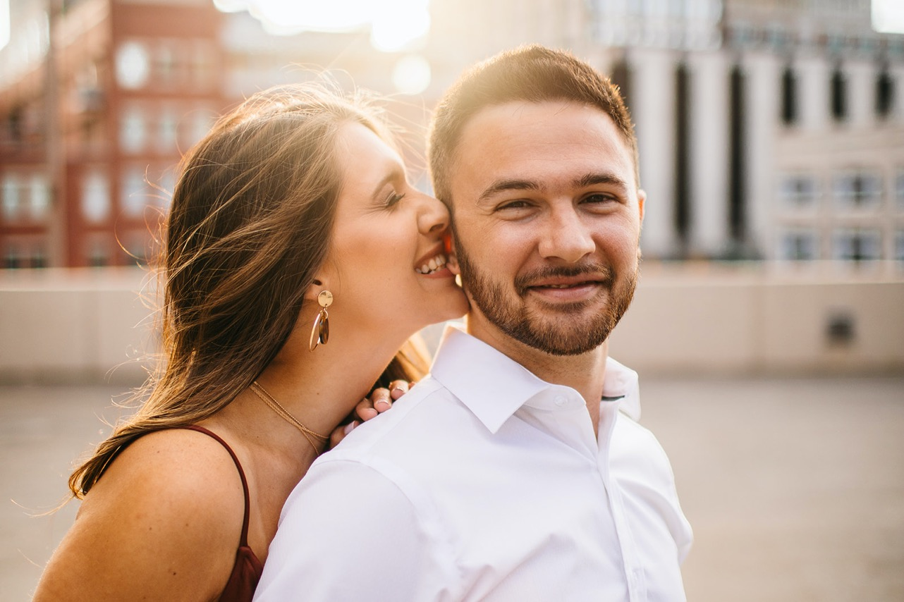 Woman giggles into her fiance's ear during their engagement photo session.