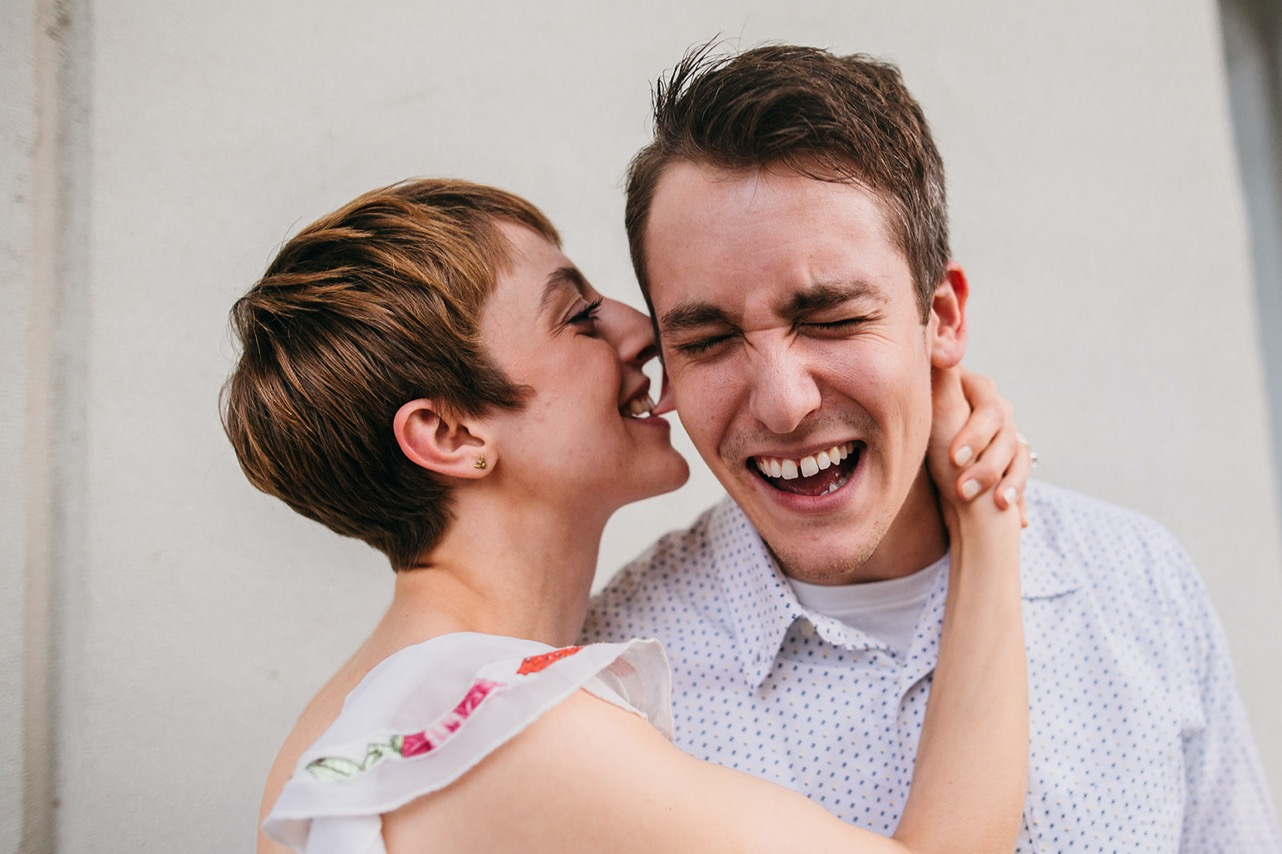 A woman bites her fiancé's ear while he laughs.