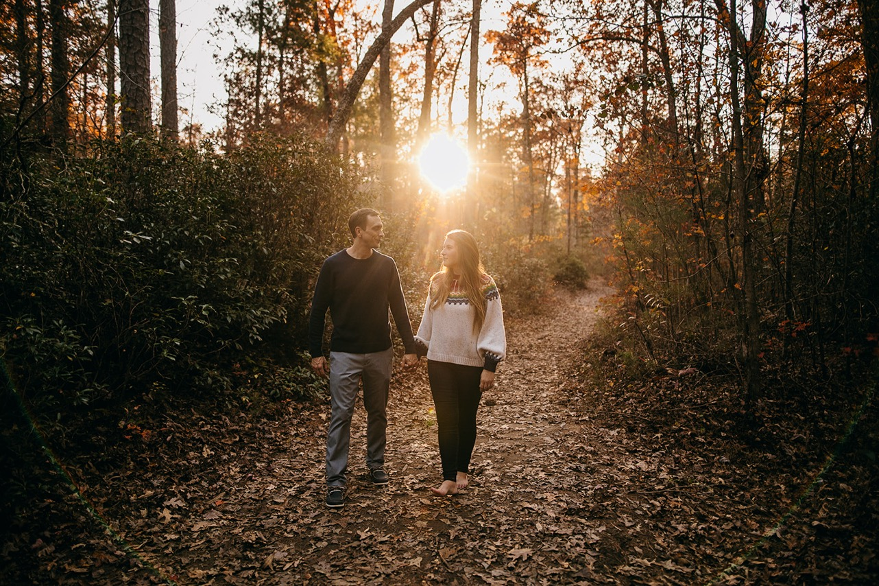 An engaged couple walk hand-in-hand on a trail in the woods at sunset.