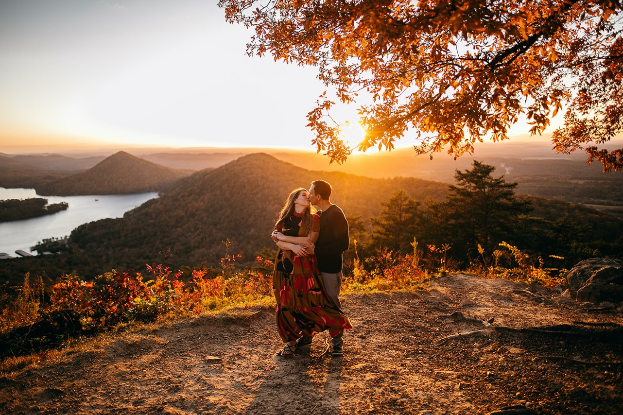 An engaged couple embrace and kiss on a ridge at sunset.