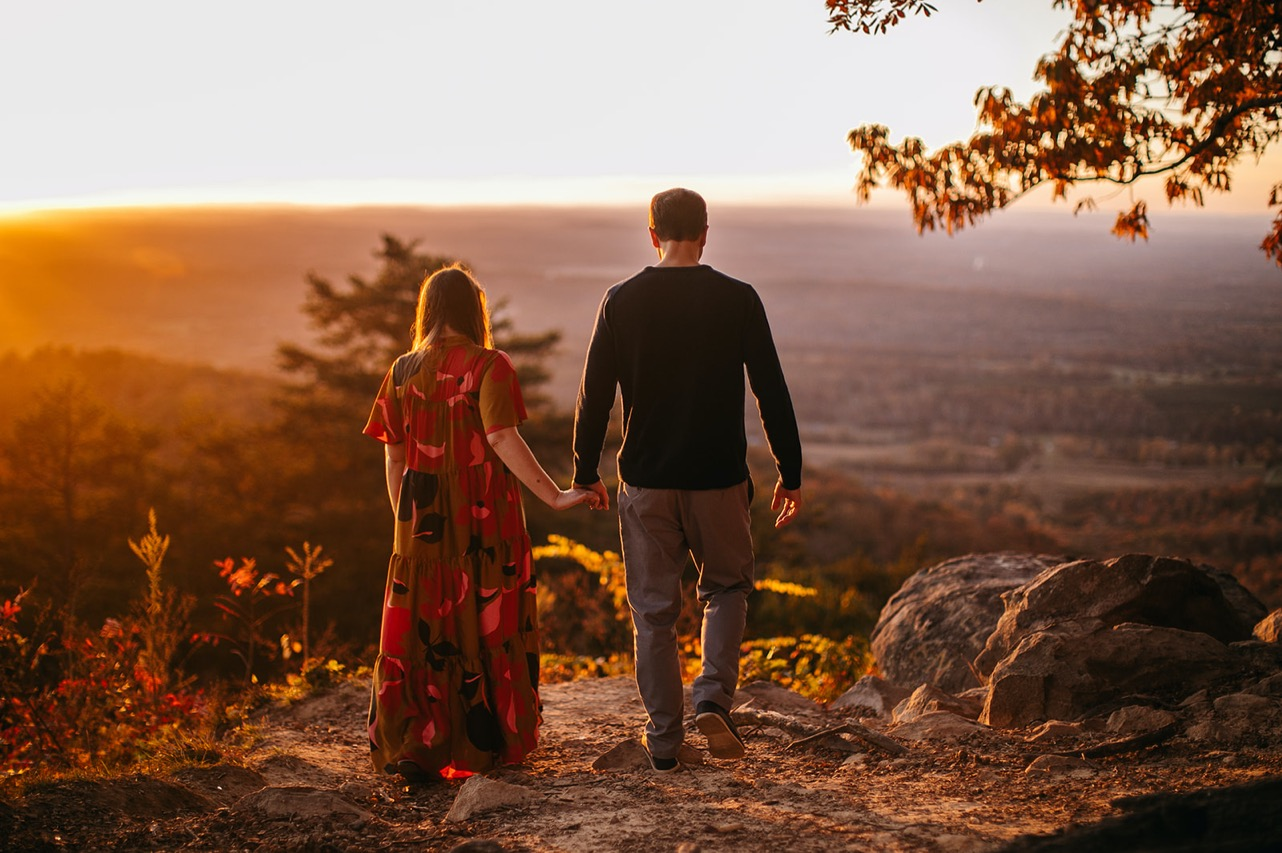 An engaged couple walk hand-in-hand onto a ridge at sunset.