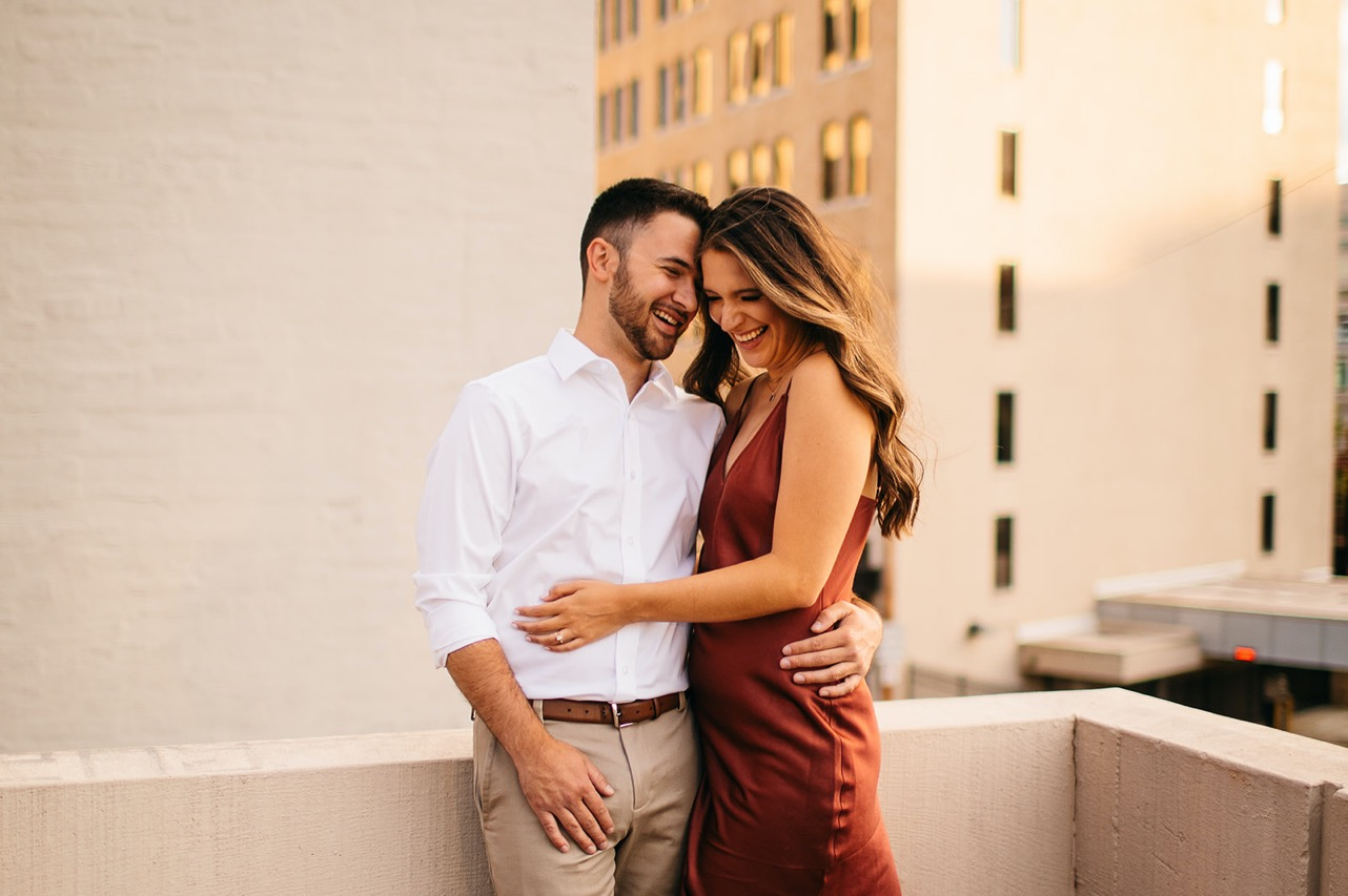 An engaged couple embraces and laughs on a rooftop in downtown Chattanooga.