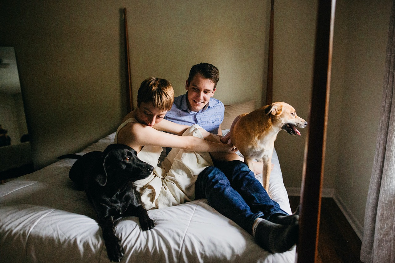 An engaged couple pose with their two dogs on their bed at home.
