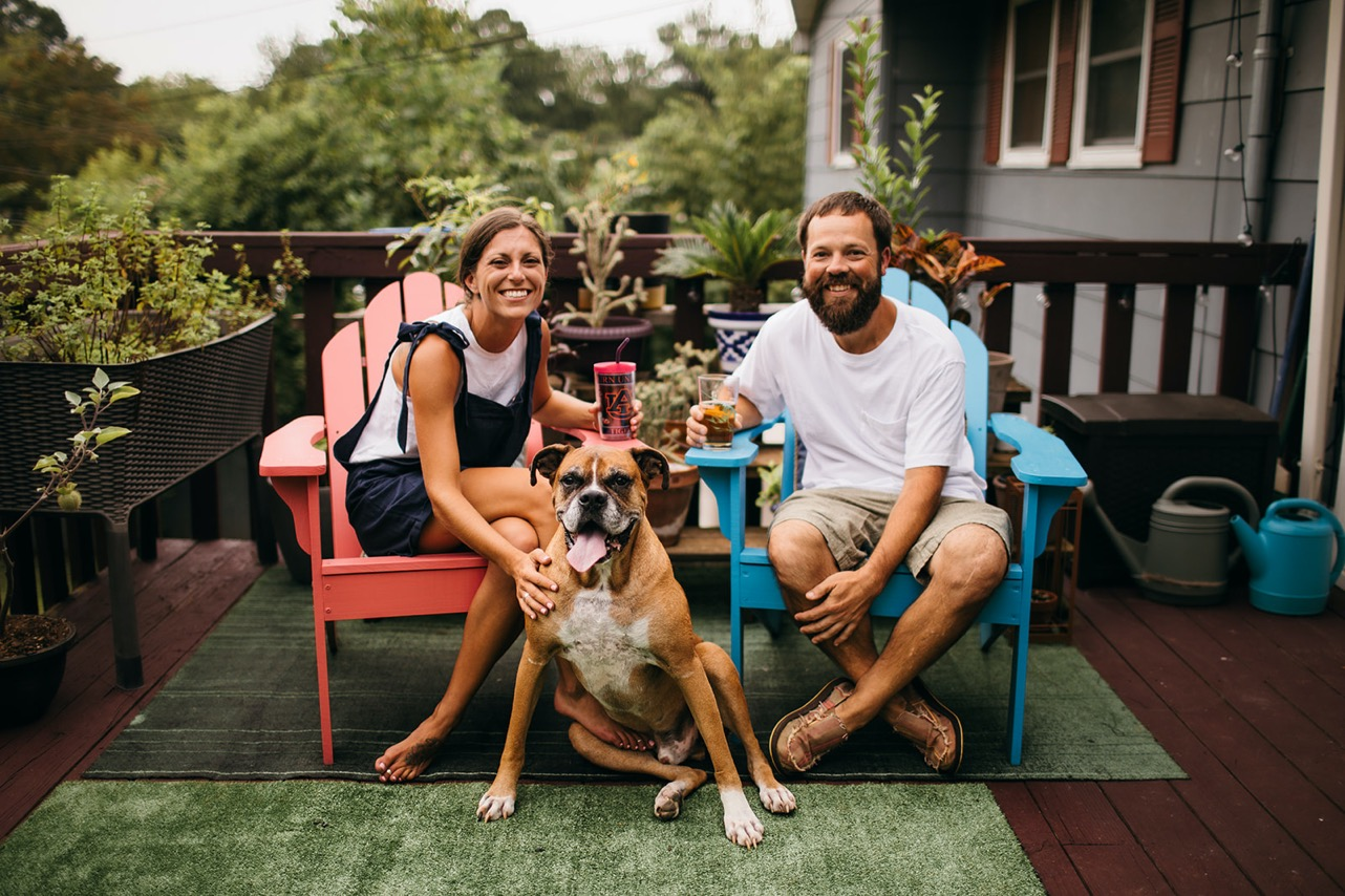 A couple share a drink on their patio in red and blue patio chairs. Their old dog sits between them.