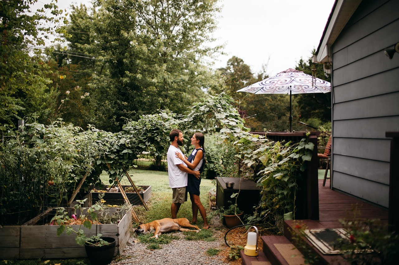 A couple stand facing one another in their backyard garden. Their old dog naps at their feet.