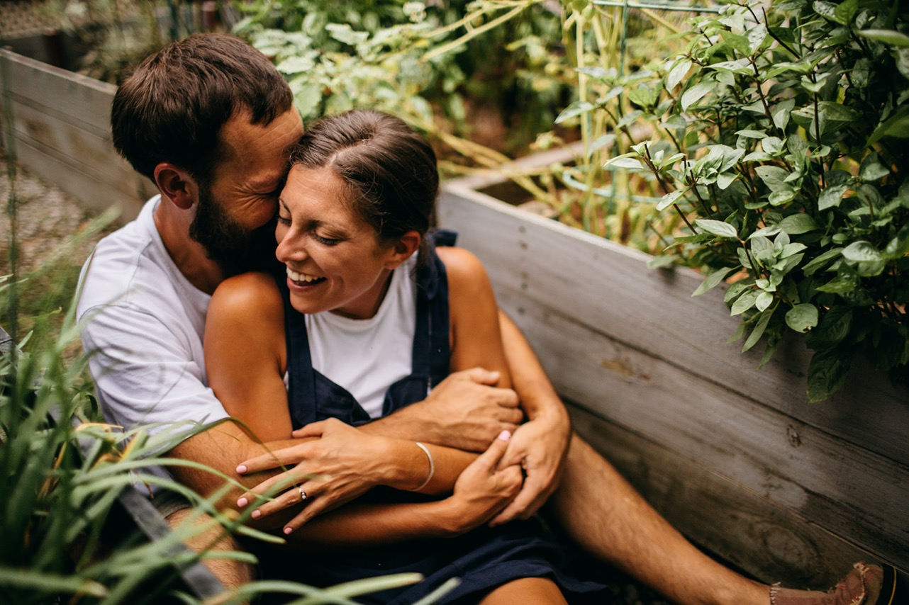 An engaged couple cuddling on the ground between two raised garden boxes in their backyard.