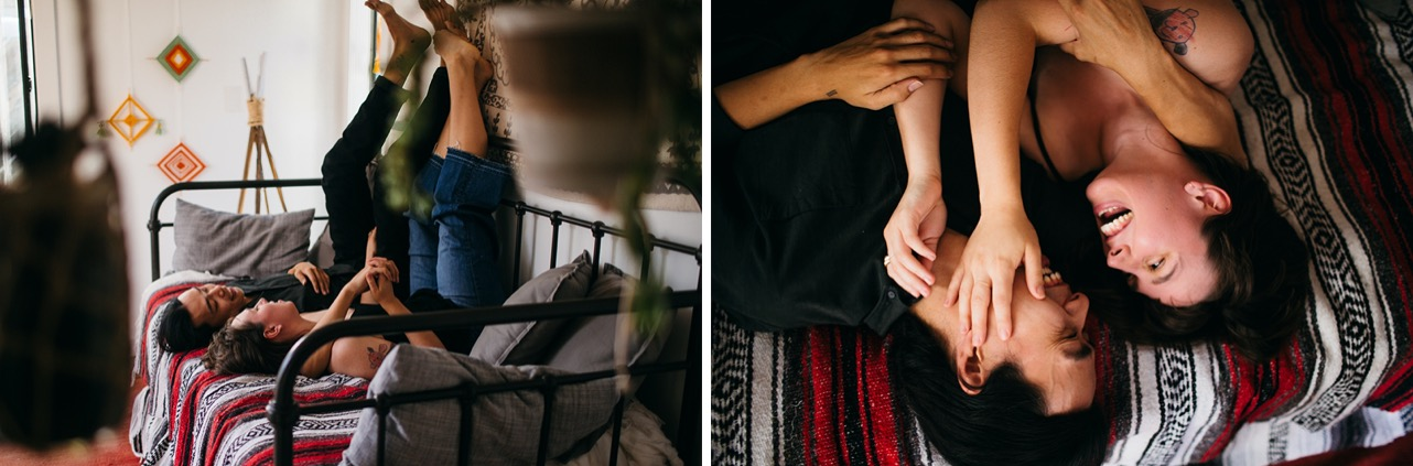 An engaged couple lay backwards on their couch with their feet up on the wall. They snuggle up for their at-home engagement photos in Chattanooga.