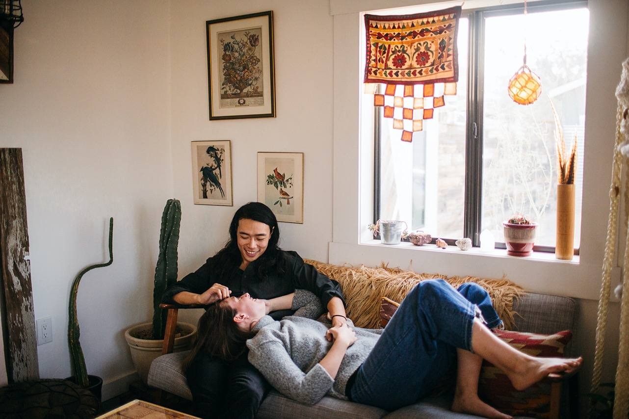 A couple cuddles on the couch together during their engagement photos at home.