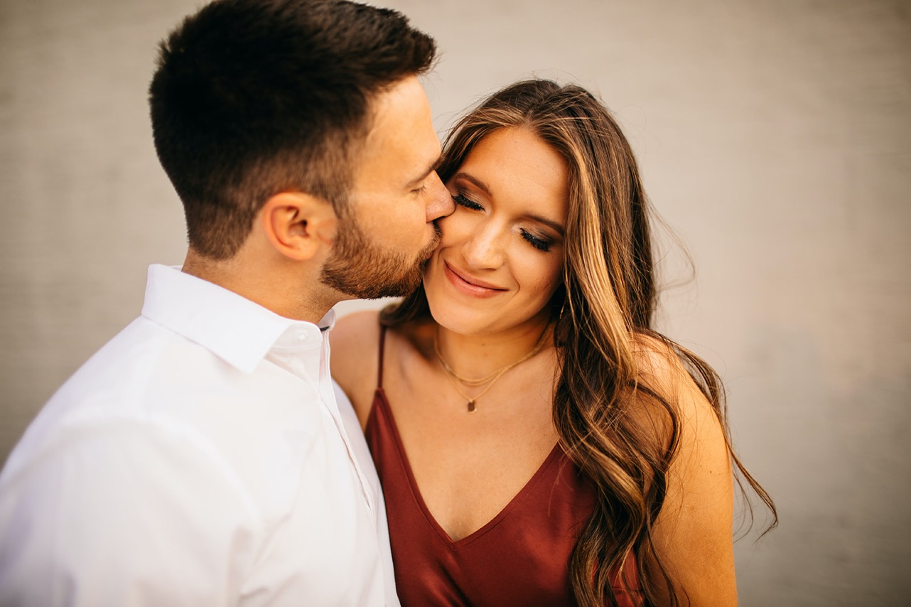 Man kisses his fiance's cheek. She's in a ruby satin dress, and he's wearing a simple white button-down shirt.