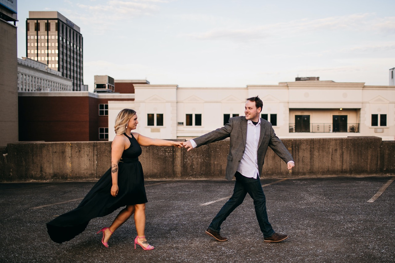 Man leads his fiance by the hand across a rooftop in downtown Chattanooga.