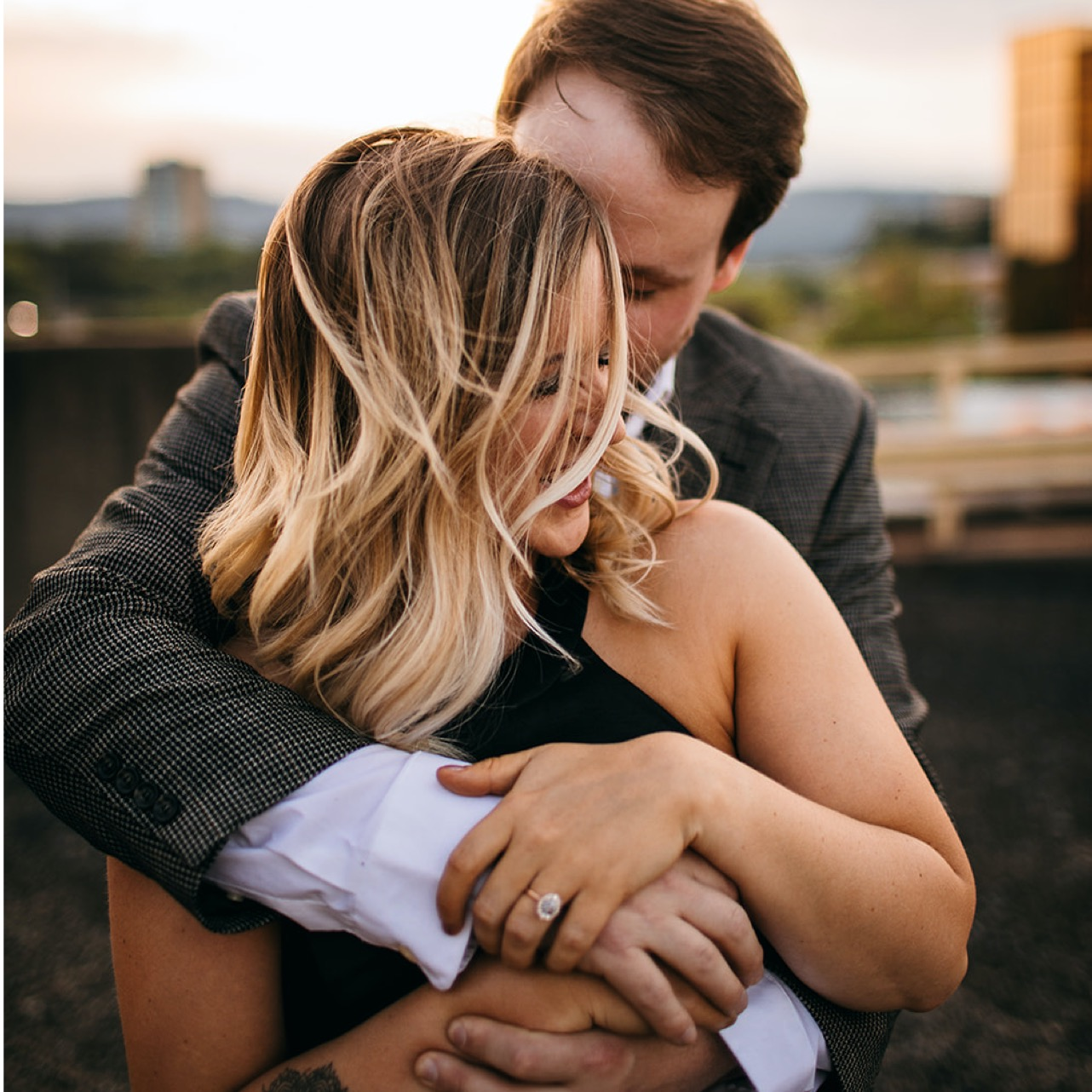 Fiances embrace on a downtown Chattanooga rooftop. You can see her oval diamond engagement ring.