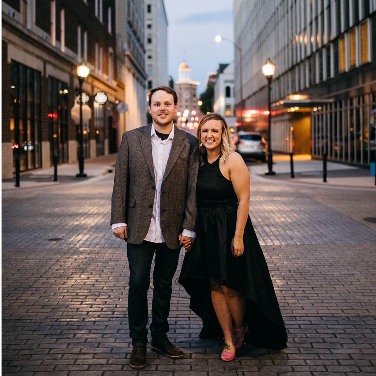 An engaged couple stands together on a street in Chattanooga at dusk. They smile and hold hands for a photo.