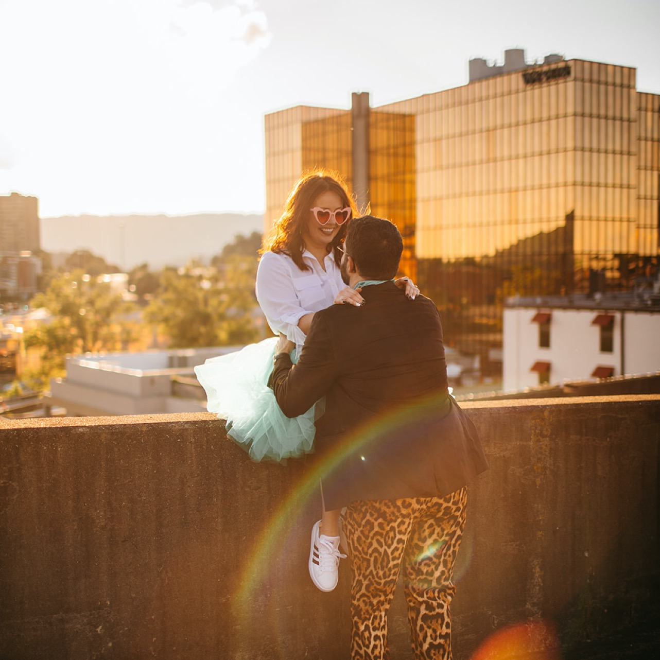 An engaged couple embraces against a barrier on a downtown Chattanooga rooftop.