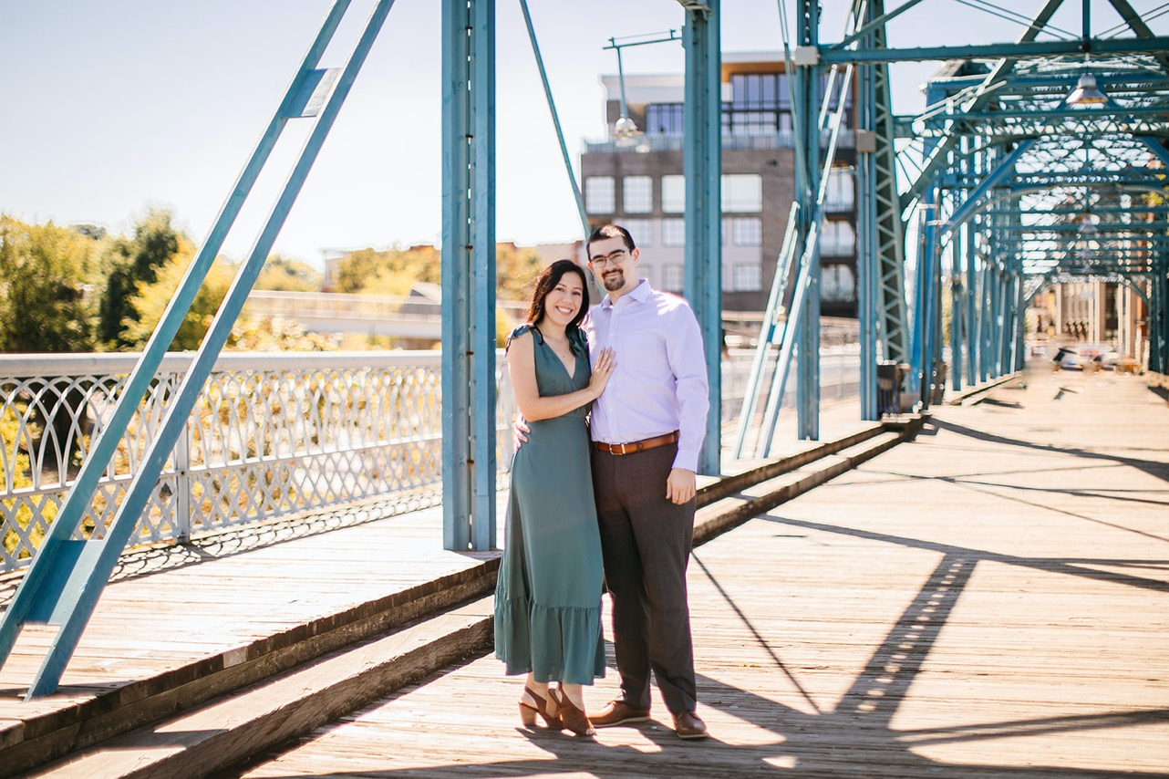 A couple smiles and poses together on the Walking Bridge in Chattanooga.