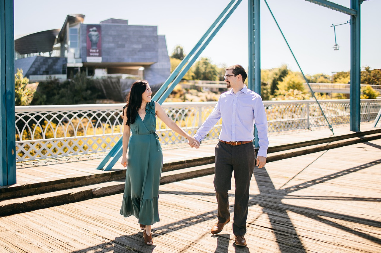 An engaged couple poses hand-in-hand and gaze at each other on the Walking Bridge in Chattanooga.