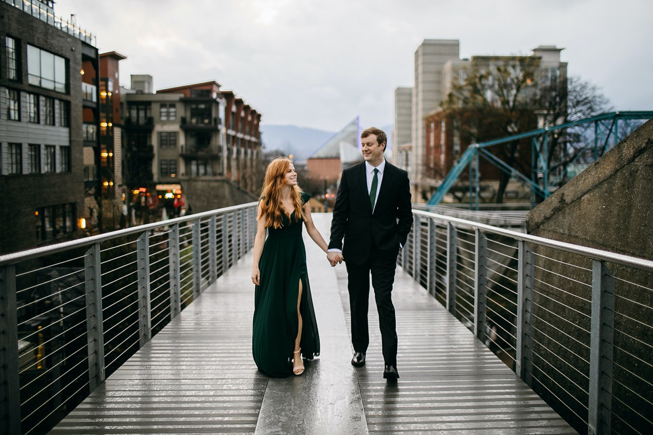 An engaged couple in formal black attire walk hand-in-hand on the Walking Bridge in Chattanooga.