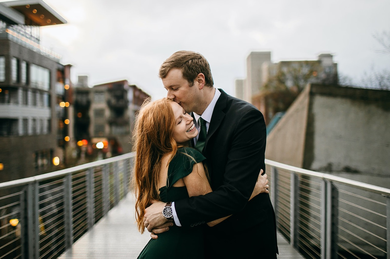 An engaged couple embraces during their engagement photos on the Walking Bridge in Chattanooga. The man kisses the woman's forehead as she laughs.