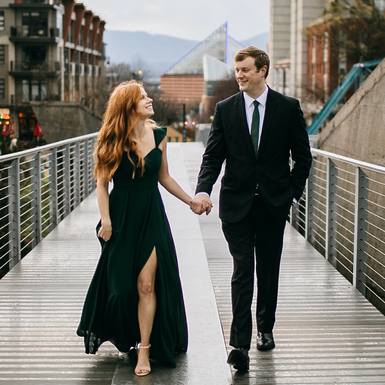 An engaged couple walks hand-in-hand on the Walking Bridge during their Chattanooga engagement photos.