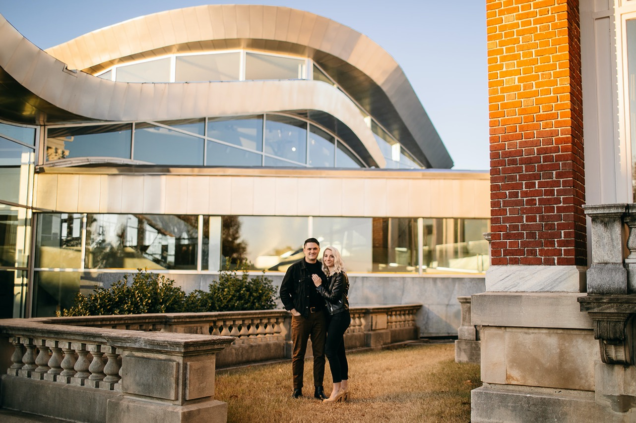 A couple poses in front of a modern-looking building at sunset near the Walking Bridge in Chattanooga.