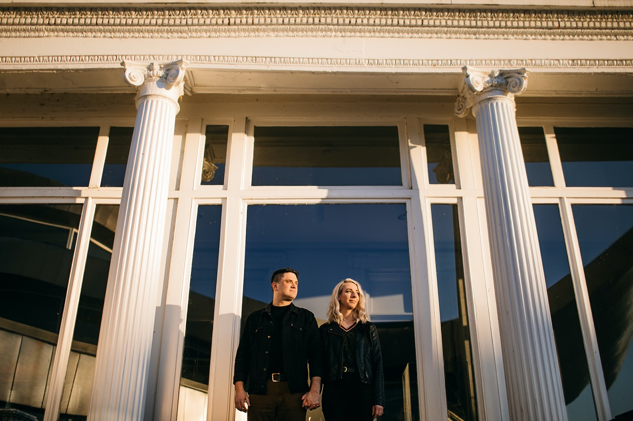 An engaged couple poses together in front of a building between two white columns.