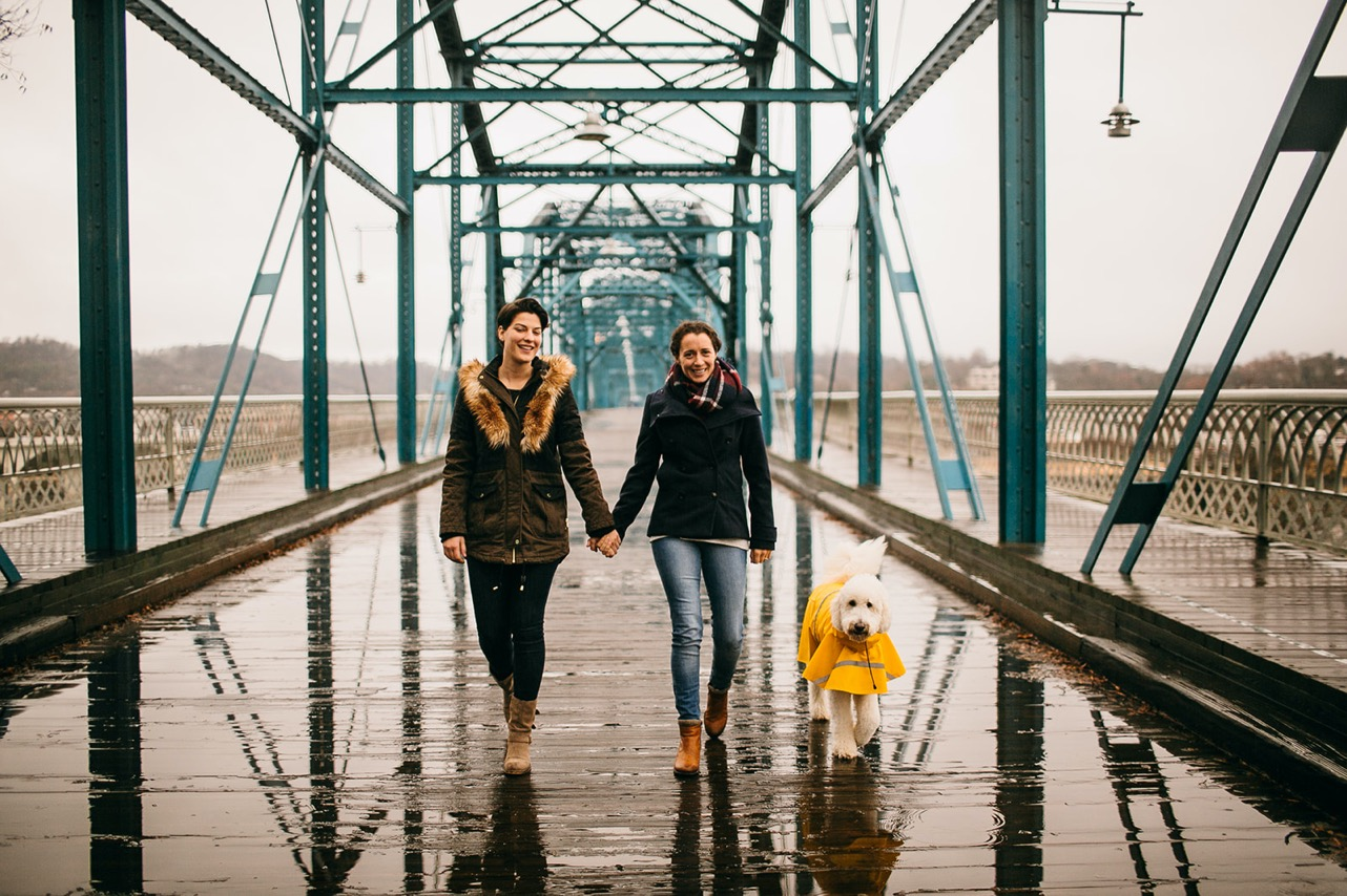 An engaged lesbian couple walks their white goldendoodle wearing a yellow raincoat in the rain on the Walking Bridge.