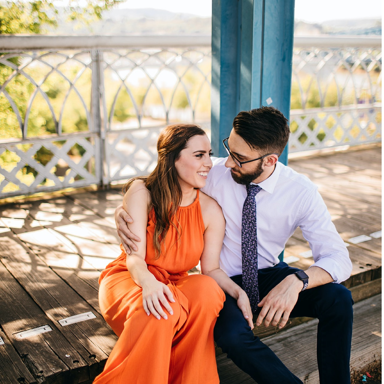 A couple sits together, embracing and looking into each other's eyes, on the Walking Bridge in Chattanooga.